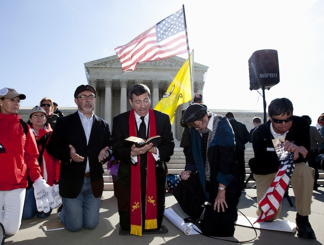 Protesters pray in front of the Supreme Court during oral arguments. (Carolyn Kaster/AP)