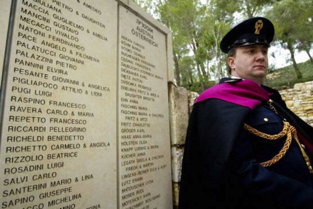 An Italian policeman stands guard over a wall honoring Giovanni Palatucci and others in 2005 (Gali Tibbon/AFP/Getty Images)
