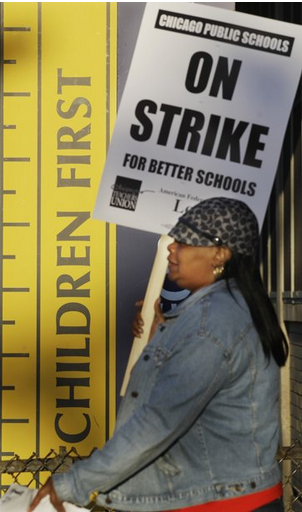 Chicago teacher Alma Hill walks a picket line outside Benjamin Banneker Elementary School in Chicago. (M. Spencer Green/AP)