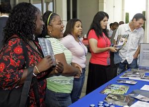 Job fair attendees look over a recruiting table. AP Photo/Nick Ut