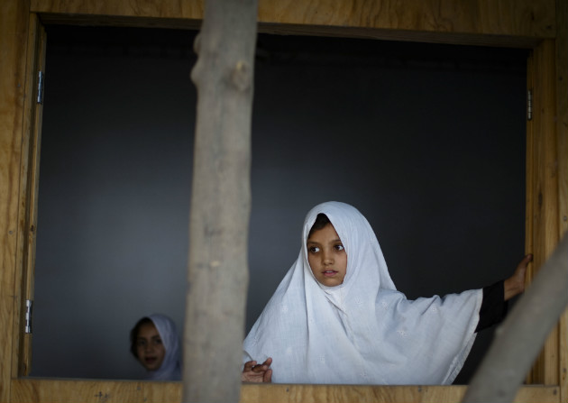 A girl peeks out of a classroom window at a school in Kandahar, Afghanistan, Oct. 1, 2011. (Anja Niedringhaus/AP)