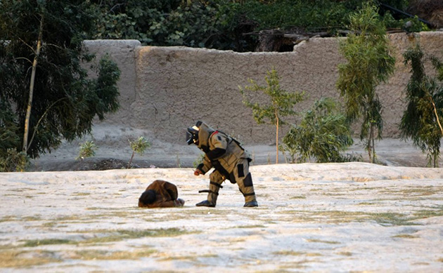 An Afghan bomb technician in a protective suit approaches a suicide bomber. (Parwiz/Reuters)