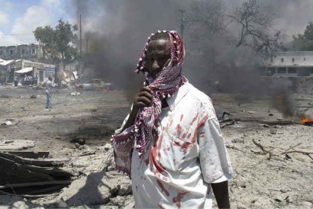 A wounded man stands at the scene of an explosion in Somalia. (AP/File)