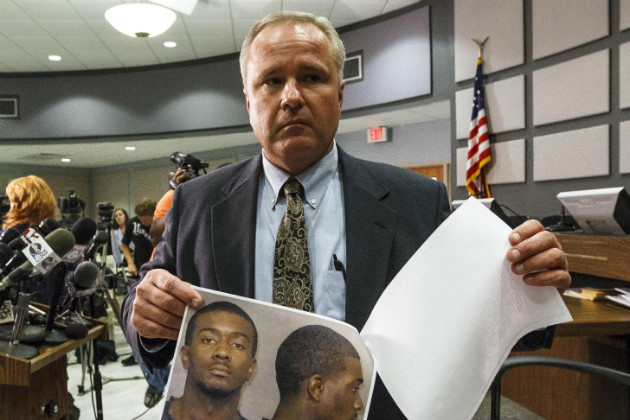 Auburn Police Chief Tommy Dawson shows headshots of suspect Desmonte Leonard during a news conference, June 10, 2012. (Vasha Hunt/AP)