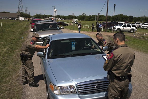 Officers talk to residents before clearing them to return to their homes in West Texas (Adrees Latif/Reuters)