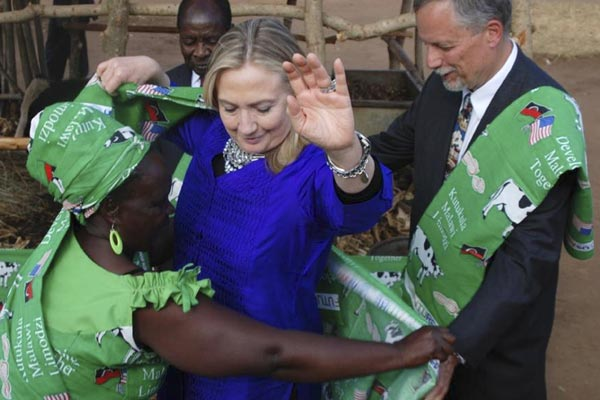 U.S Secretary of State Hillary Clinton is helped into Malawi garb by Emmie Phiri, chairperson of a dairy farmers group, during her visit to Malawi on Aug. 5, 2012. (Reuters)