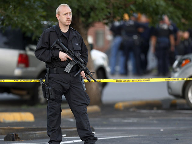 A SWAT team officer stands watch near an apartment house where the suspect in a shooting at a movie theater lived in Aurora, Colo., Friday, July 20, 2012. (Ed Andrieski/AP)