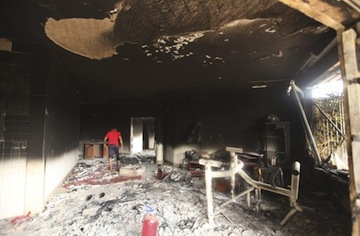 A man walks inside the U.S. Consulate, which was attacked and set on fire by gunmen yesterday. (Esam Al-Fetori/Reuters)