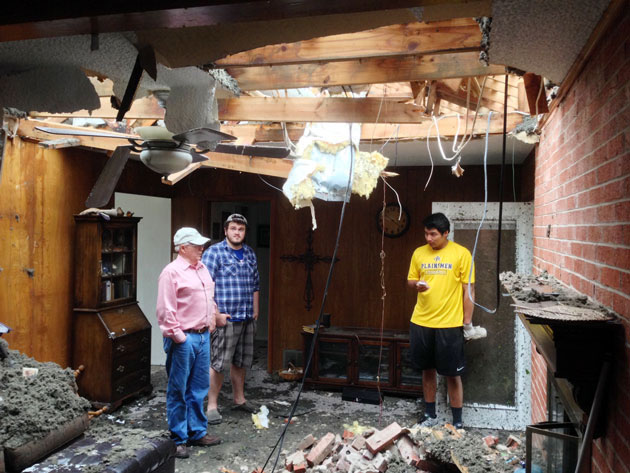 Ethan Jones (center) and German Hernandez help clear out Bill Jones' destroyed home. (Jason Sickles/Yahoo News)