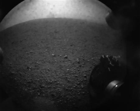 This handout image from NASA, one of the first images from the Curiosity rover which landed on Mars the evening of August 5, 2012, with camera dust cover in place, shows the wheel of the rover after it successfully landed on Mars. (REUTERS/Courtesy NASA)