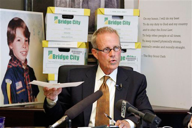Oregon attorney Kelly Clark speaks in front of former court case illustrations and boxes full of records from the Boy Scouts of America. Nearly 20,000 pages of the confidential files will soon be made public. (Don Ryan/AP)