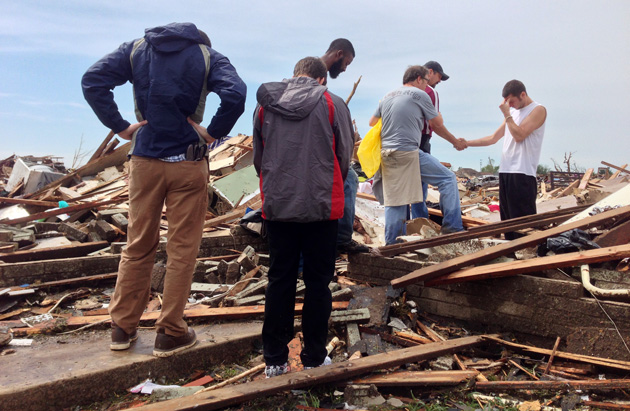A group of men pray with tornado survivor Tim Wardwell. (Jason Sickles/Yahoo News)