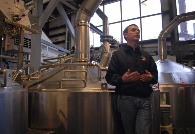 The Alaska Brewing Co.'s Brandon Smith stands in front of his company's new broiler system that uses spent grains to generate power (AP/Joshua Berlinger)