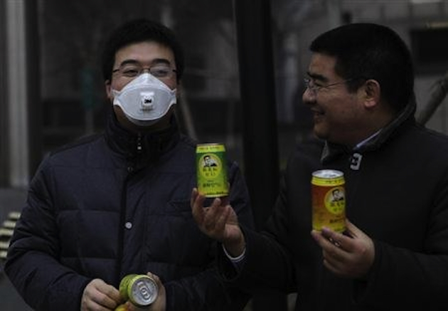 "Chen Guangbiao offers a sample of his canned ""fresh air"" to a passerby in China (Reuters)"