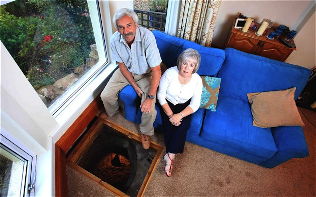Colin and Vanessa Steer sit near the medieval well below their living room floor. (SWNS)