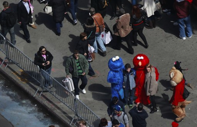 Individuals dressed as Cookie Monster and Elmo pose for pictures in Times Square (Reuters)