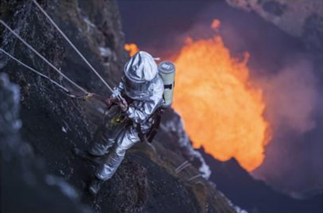 A researcher descends toward the crater of an active volcano. (Discovery Channel)