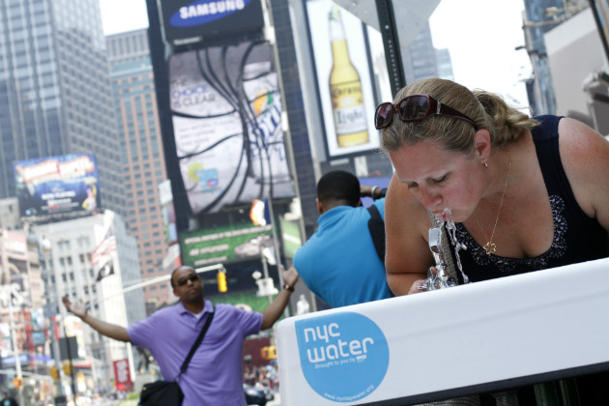 A woman drinks New York City tap water in New York's Times Square. (Mary Altaffer/AP)
