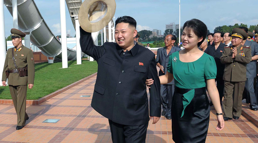 North Korean leader Kim Jong Un, center, accompanied by his wife Ri Sol Ju, right, waves to the crowd as they inspect the Rungna People's Pleasure Ground in Pyongyang. (AP Photo/Korean Central News Agency via Korea News Service)