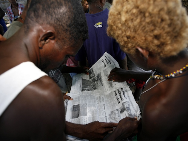 Two Solomon Islands residents reading a newspaper (AP/Rob Griffith)