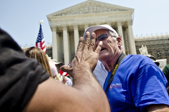 Protesters argue about the health care law outside the Supreme Court. (Kris Connor/Getty Images)