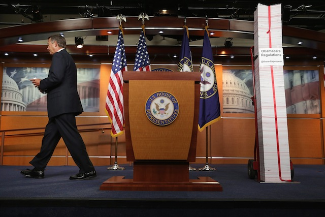 John Boehner walks away from a printed version of Obamacare regulations. (Chip Somodevilla/Getty Images)