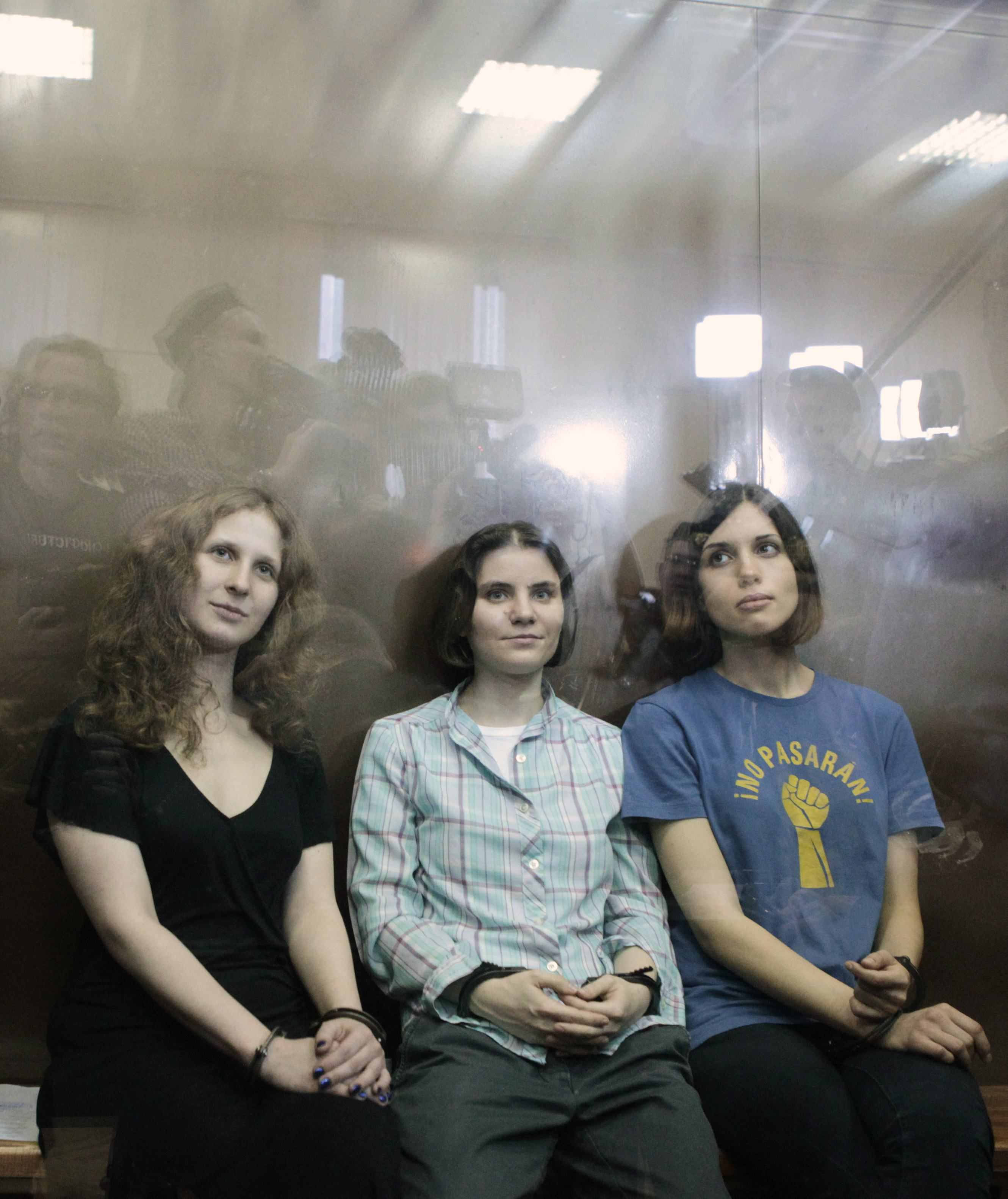 "Members of the female punk band ""Pussy Riot"" sit in a glass-walled cage after a court hearing in Moscow (Maxim Shemetov/Reuters)"