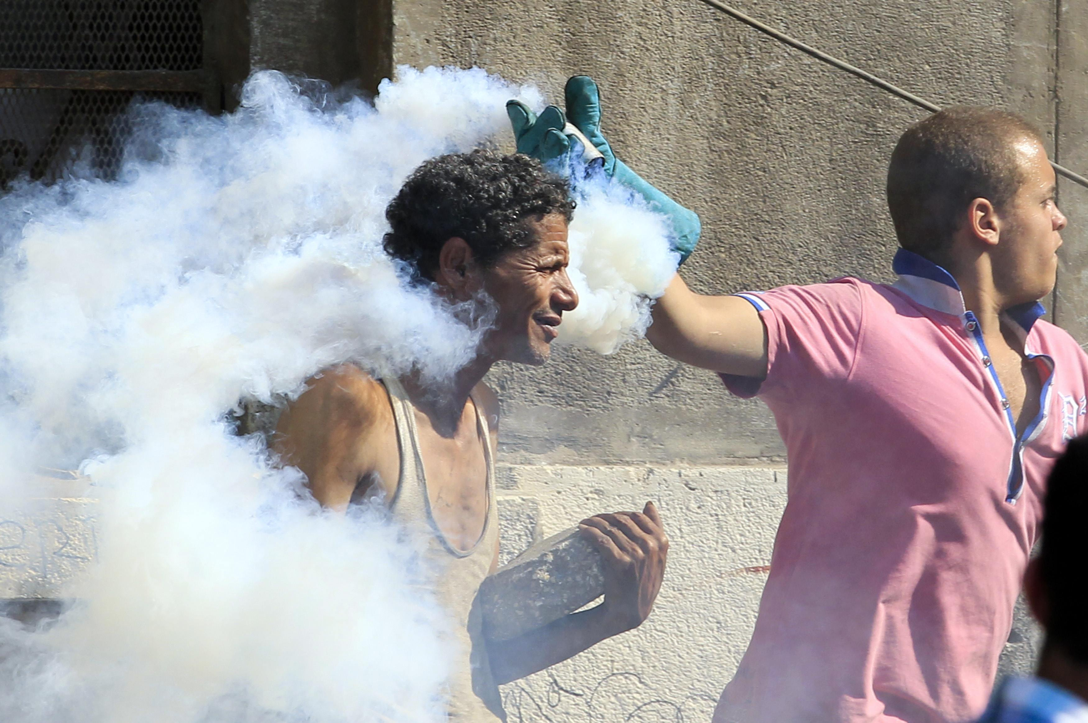 An Egyptian protester throws a tear gas canister, which was earlier thrown by riot police,and another throws a stone during clashes along a road which leads to the U.S. embassy, near Tahrir Square in Cairo. (Mohamed Abd El Ghany/Reuters)