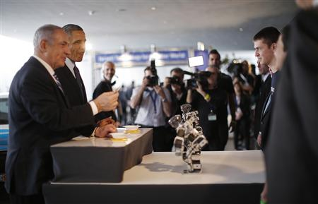 President Barack Obama (2nd L) and Israeli Prime Minister Benjamin Netanyahu (L) eat Matzo bread delivered to them by miniature robots (C) as they tour a technology expo at the Israel Museum in Jerusalem March 21, 2013. (Jason Reed/Reuters)