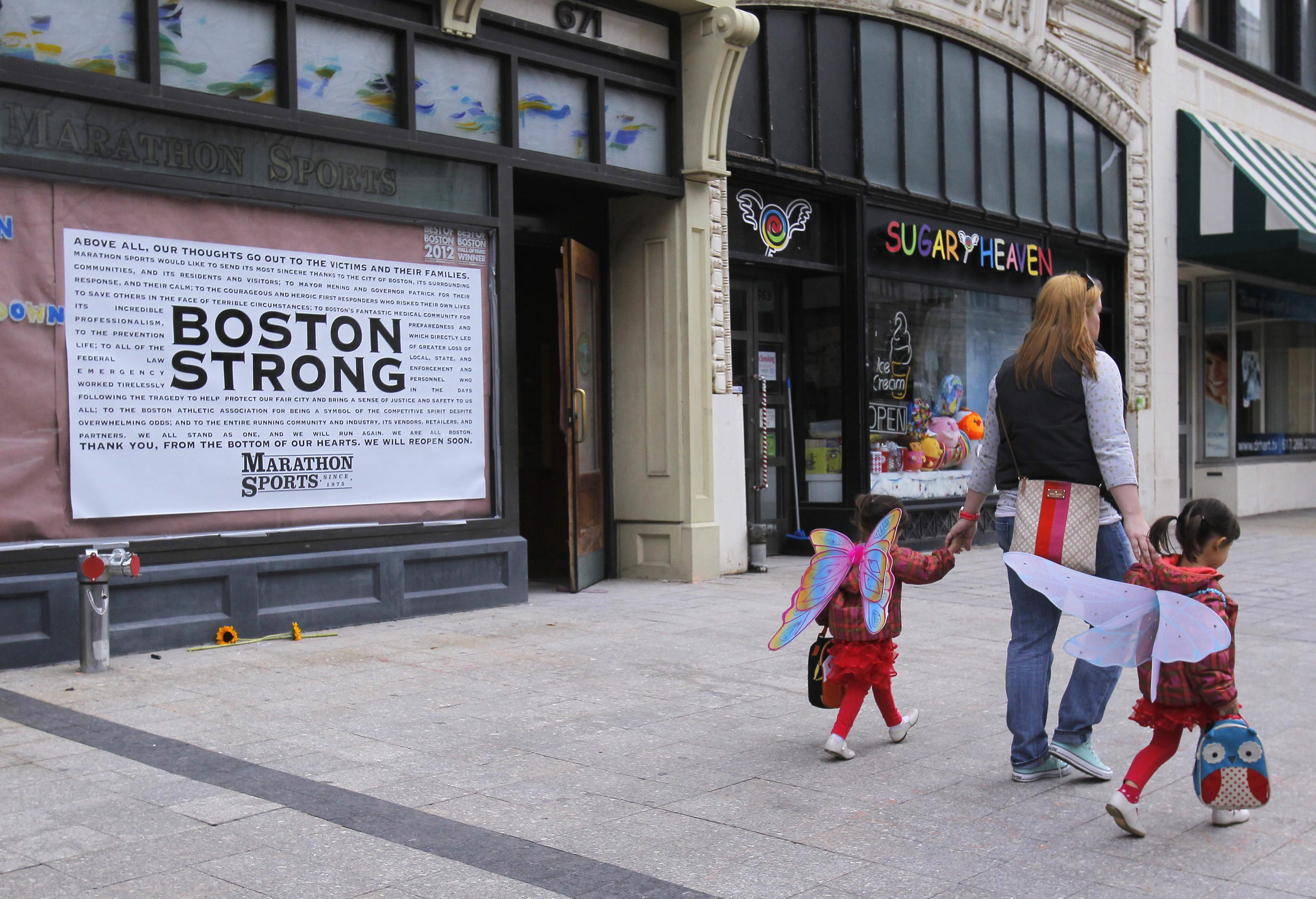 A woman and her children walk past the site of the first explosion on Boylston Street in Boston, April 24, 2013. (Jessica Rinaldi/Reuters)