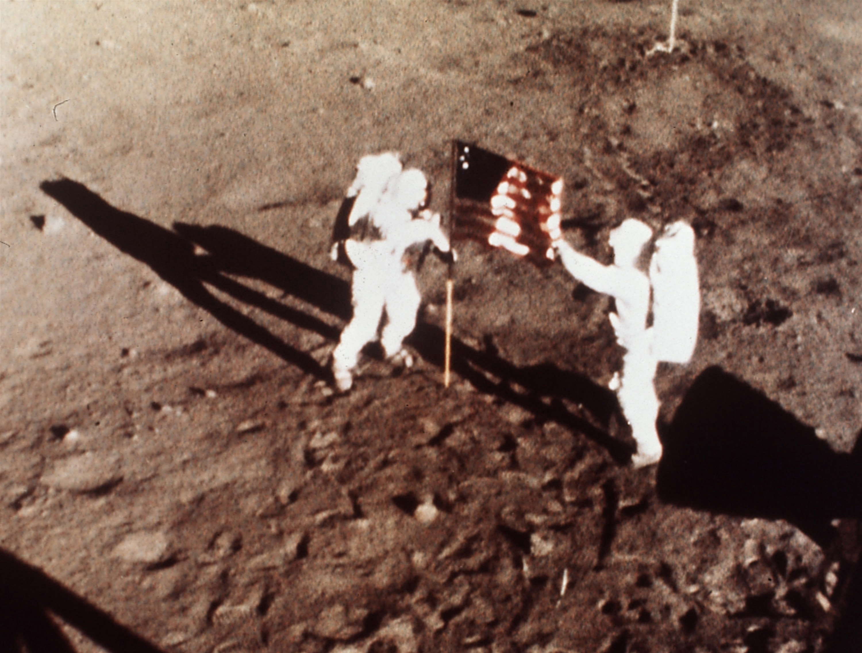 "Apollo 11 astronauts Neil Armstrong and Edwin E. ""Buzz"" Aldrin, the first men to land on the moon, plant the U.S. flag on the lunar surface on July 20, 1969. (NASA/AP)"
