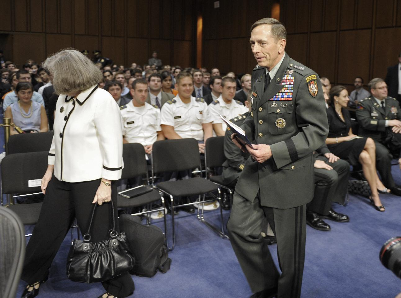 Holly Petraeus and Gen. David Petraeus walk past a seated Paula Broadwell (rear right) at his confirmation hearing as CIA director in June 2011. (Cliff Owen/AP)