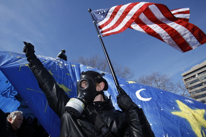 Occupy DC supporter Joseph Moehrl, 23, waves an American flag at a recent demonstration (Jacquelyn Martin/AP)