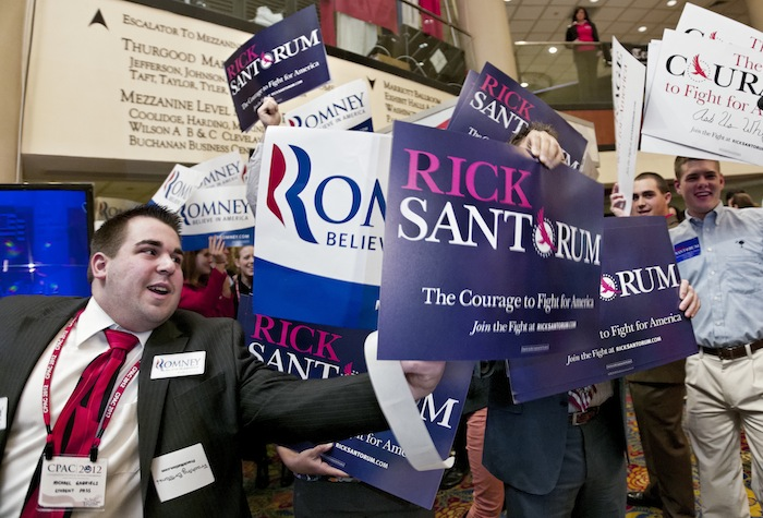 Volunteers supporting Rick Santorum and Mitt Romney vie for attention at the Conservative Political Action Conference (J. Scott Applewhite/AP))