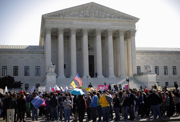 Protesters and supporters rally at the Supreme Court during health care arguments Mar. 27 (Charles Dharapak/AP)