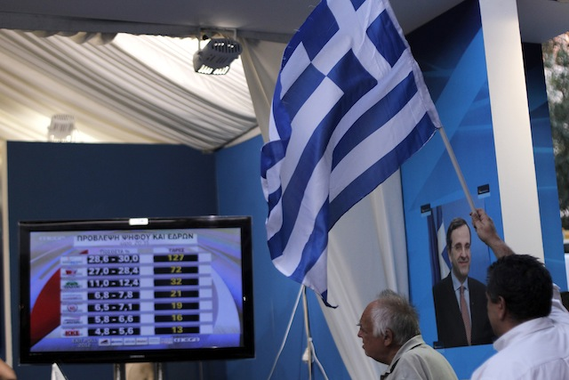 Greeks watch the returns from their elections (Petros Giannakouris/AP)