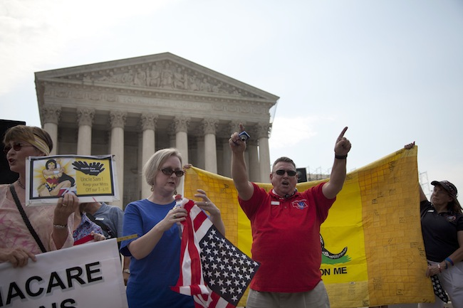 Demonstrators stand outside the Supreme Court in Washington, Monday, June 25, 2012. (Evan Vucci/AP)