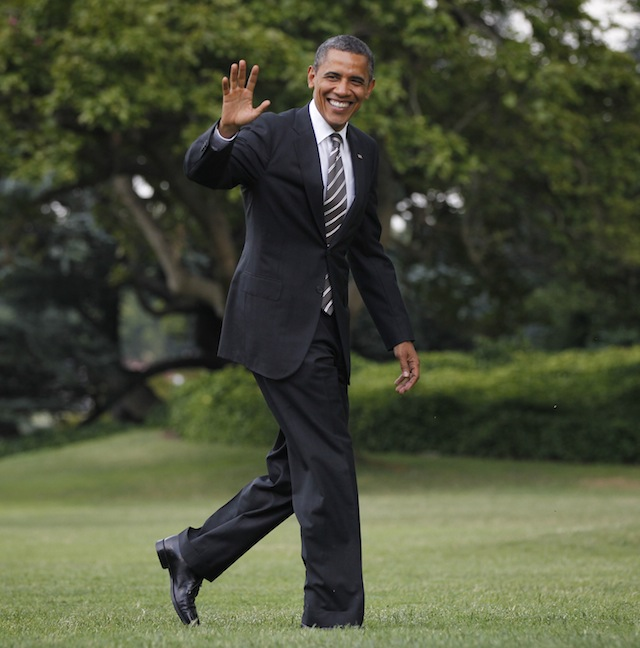President Barack Obama waves as he walks across the South Lawn of the White House on Tuesday. (Pablo Martinez Monsivais/AP)