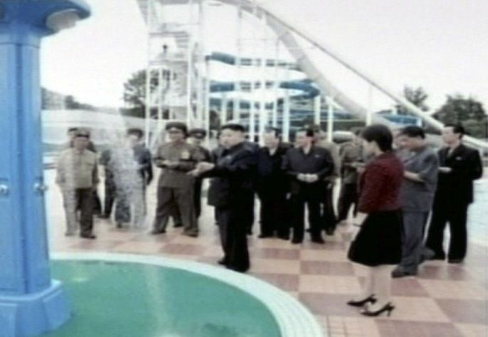 North Korean media on identified the woman seen accompanying North Korean leader Kim Jong Un recently as his wife, Ri Sol Ju. They are seen (in foreground) Tuesday July 24, 2012, attending a ceremony to mark the completion of an amusement park facility in Pyongyang. (KRT TV/AP)