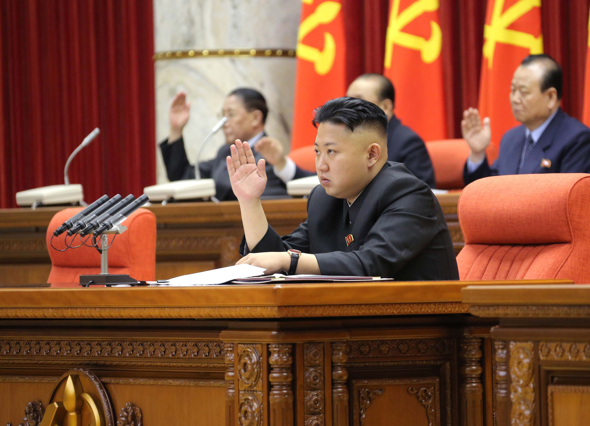 North Korean leader Kim Jong Un raises his hand with other officials to adopt a statement during a plenary meeting of the Central Committee of the ruling Workers' Party in Pyongyang, N.K. (AP/KCNA via KNS)