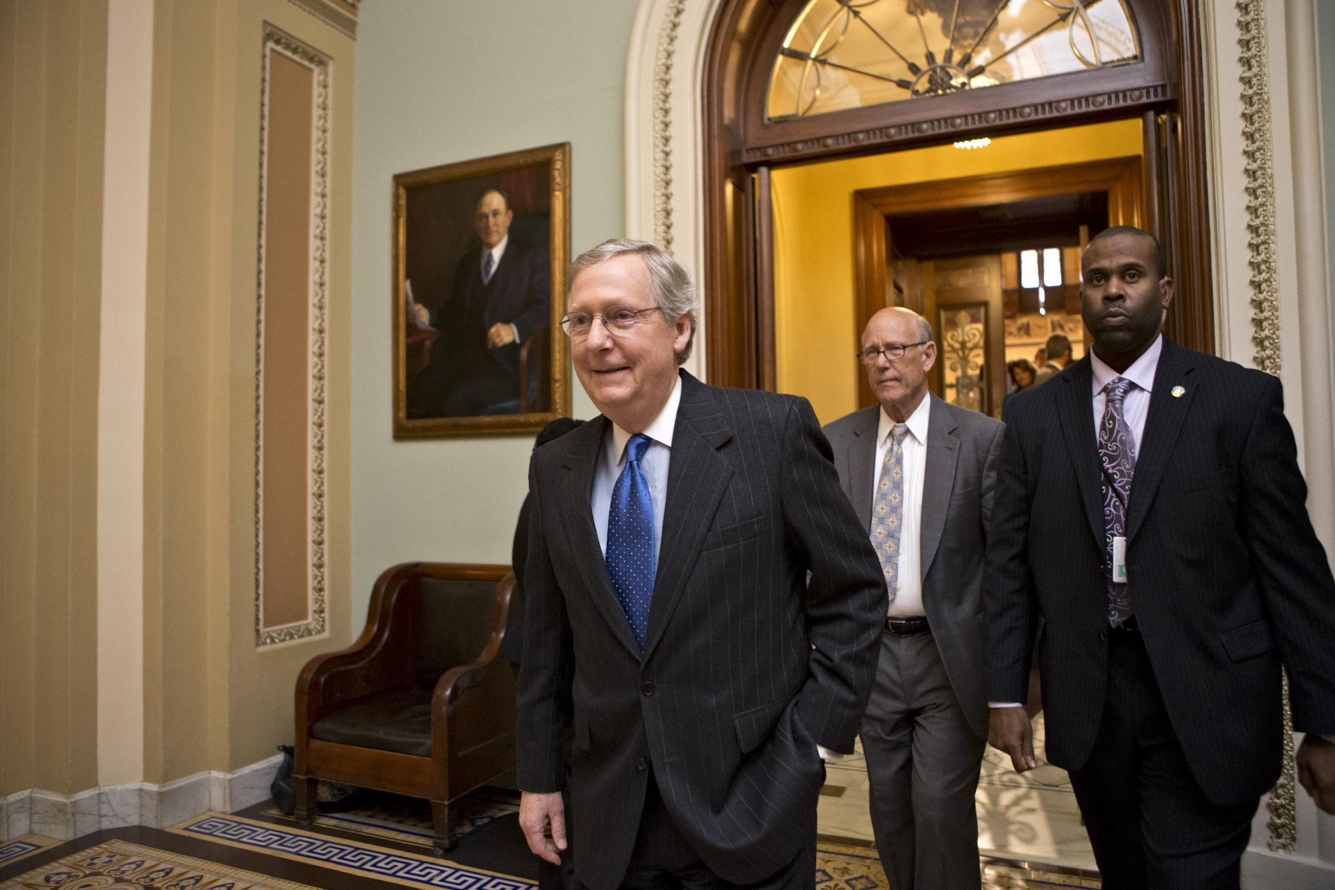 "Senate Minority Leader Mitch McConnell, R-Ky., followed by Sen. Pat Roberts, R-Kan., second from right, leaves the Senate chamber to meet with fellow Republicans in a closed-door session as the ""fiscal cliff"" negotiations continue at the Capitol. (J. Scott Applewhite/AP)"