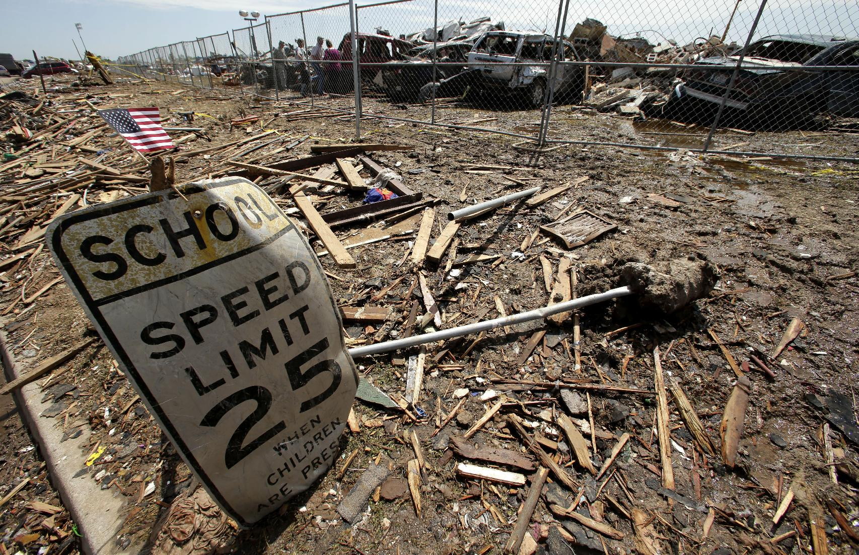 A battered sign stands outside the wreckage of Plaza Towers Elementary School in Moore, Okla. (Charlie Riedel/AP)