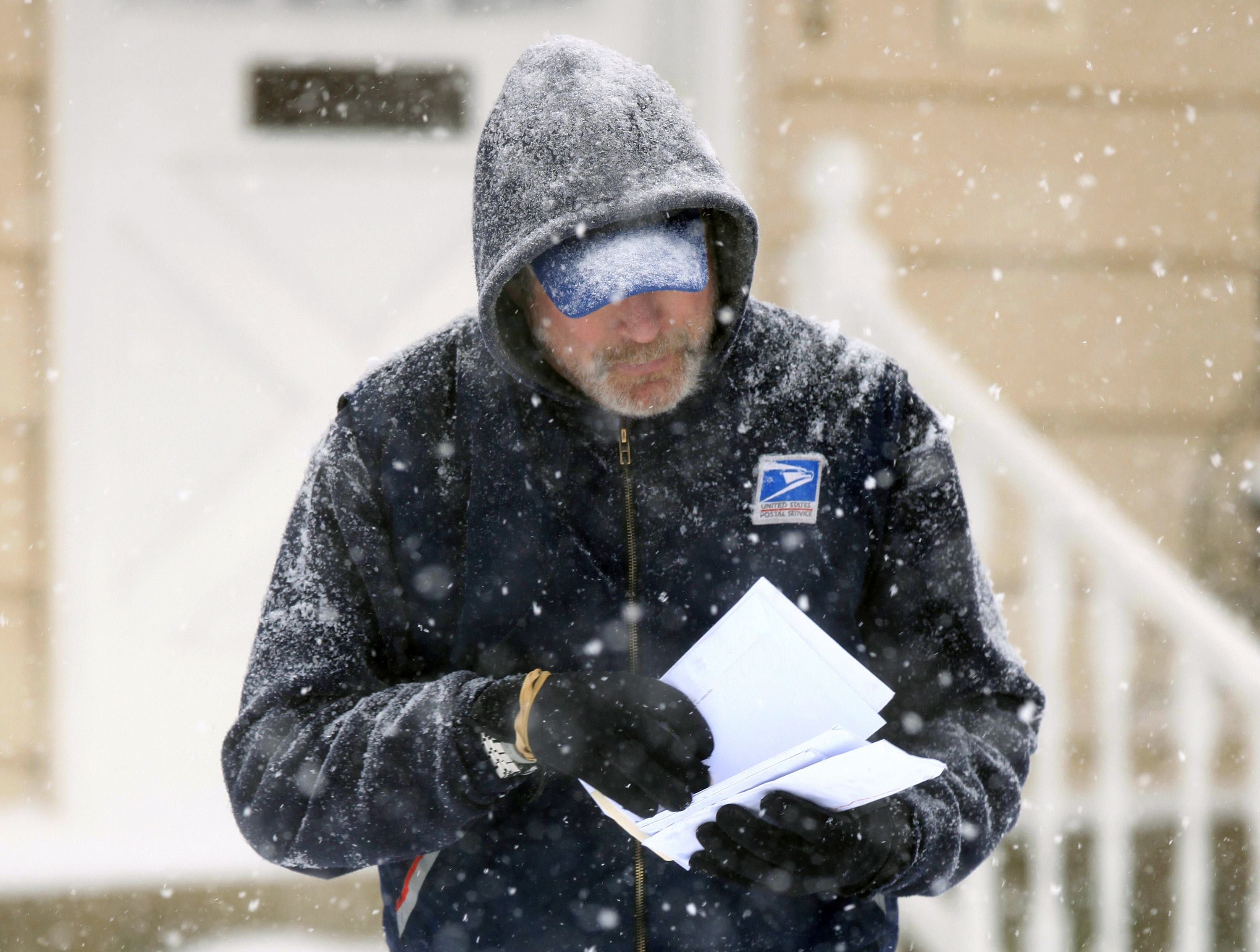 This Saturday Dec. 19, 2009 photo shows U.S. Post Office letter carrier Tim Bell delivering the mail during a snow storm in Havertown, PA. (Jacqueline Larma/AP)