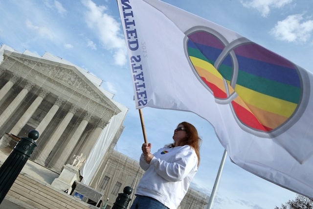 A same sex marriage supporter waves a gay pride flag outside the Supreme Court (Chip Somodevilla/Getty Images)