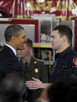President Barack Obama shakes hands with Arlington County firefighter and US Marine Corps veteran Lt. Jacob Johnson, who served in Iraq. (Susan Walsh/AP)