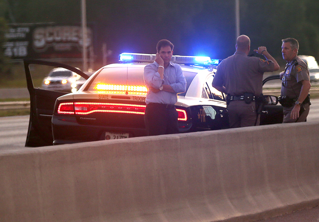 Rubio stands near a police car after leaving the Romney motorcade (Justin Sullivan/Getty Images)