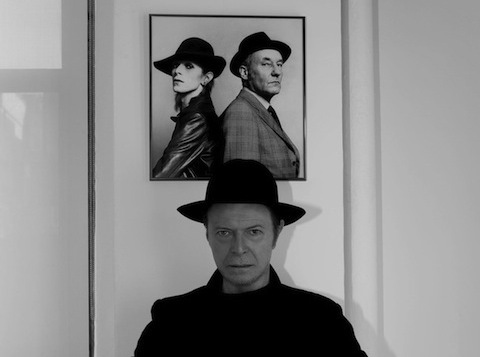 Bowie poses in front of a photo of his younger self with William S. Burroughs