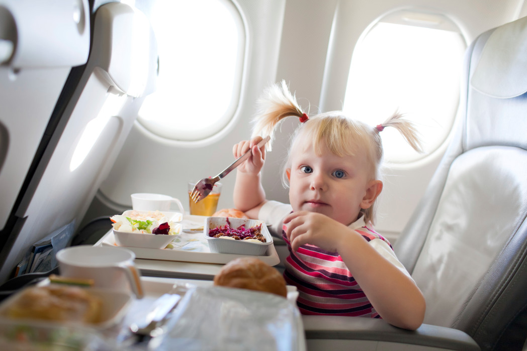 girl eating on plane
