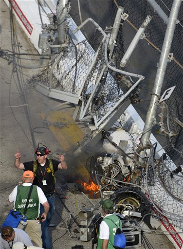 Kyle Larson's engine burns behind the wall and safety fence that he hit along the front grandstands. (AP)