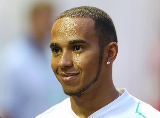 Mercedes driver Lewis Hamilton of Britain smiles as he walks at the paddock ahead of Sunday's Singapore Formula One Grand Prix on the Marina Bay City Circuit, Thursday, Sept. 19, 2013, in Singapore